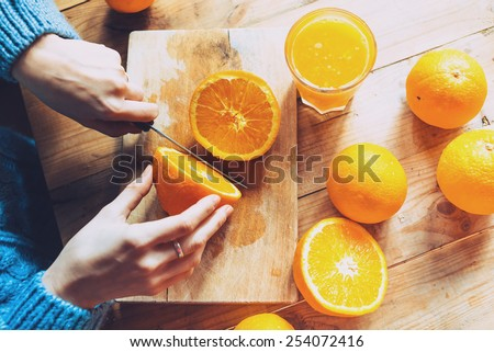 Person cutting  to make juice from fresh oranges on wooden table - stock photo