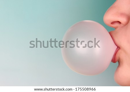 Person doing bubble with chewing gum on bright background - stock photo