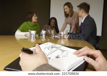 Person doodling during business meeting - stock photo