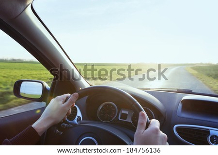 Person driving car with blue sky and green grass