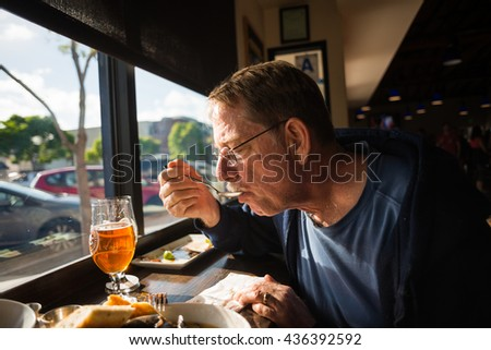 Person enjoying a meal and beer at a restaurant