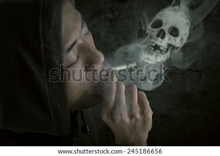 Person enjoying cigarette with smoke shaped skull, shot over black background - stock photo