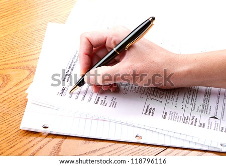 person filling out a 1040 EZ tax form - stock photo