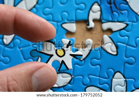 Person fitting the last puzzle piece.Business concept for completing the final puzzle piece - stock photo