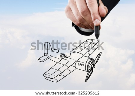 Person hand drawing old airplane on sky background - stock photo