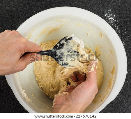 Person handling a sticky dough with black spatula in white plastic bowl on black table - stock photo