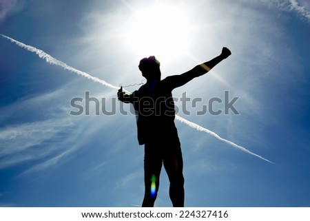 Person has attained the goal, young man rejoicing achievement raised the hands, concept victory over self, silhouette of male runner exploded to the top hill - stock photo