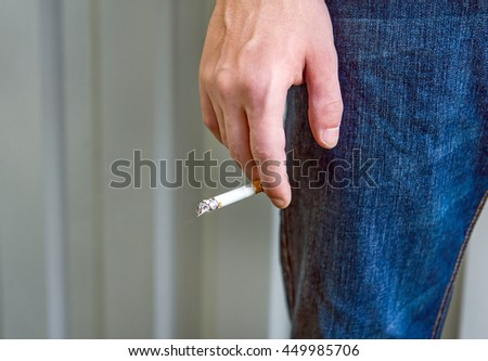 Person hold a Cigarette in the Hand closeup outdoor