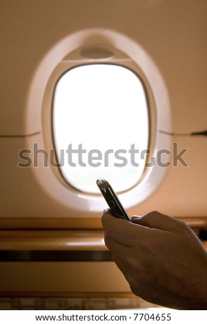 Person Holding a Business Phone While on a Plane - stock photo