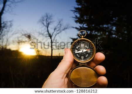 person holding an antique compass for guidance at sunset - stock photo