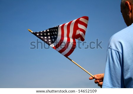 Person holding the American flag outside with a beautiful blue sky as the background. - stock photo