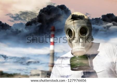 Person in a gas mask against a pipe polluting air - stock photo