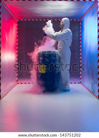 person in a protective suit and gas mask working with steaming substances over a blue waste drum marked as bio hazardous inside a containment tent - stock photo