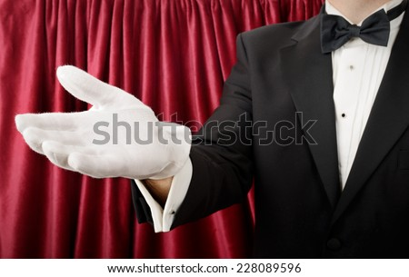 Person in a tuxedo and white gloves presenting or showing - stock photo