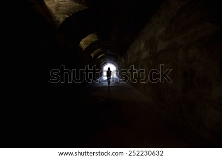 Person in dark tunnel, going towards the light.  - stock photo