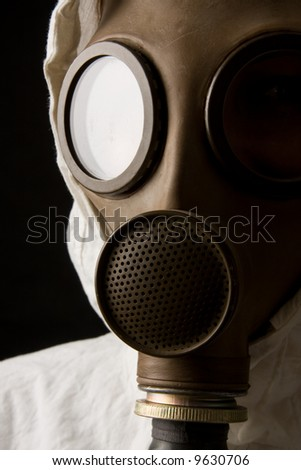 Person in gas mask on black background - stock photo