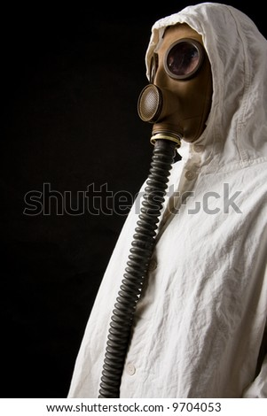 Person in gas mask on dark background - stock photo
