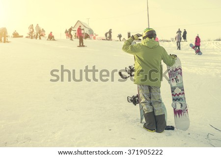 person in ski suit with snowboards looking on the hill