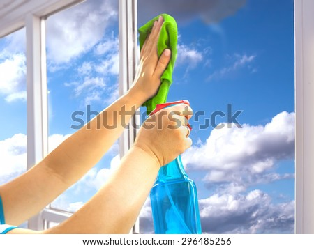Person is cleaning a window with spray - stock photo