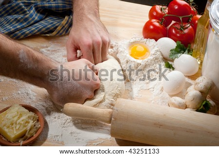 Person kneading dough on wooden table top with a lot of flour - stock photo
