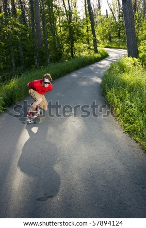 person long boarding down a scenic curved path - stock photo