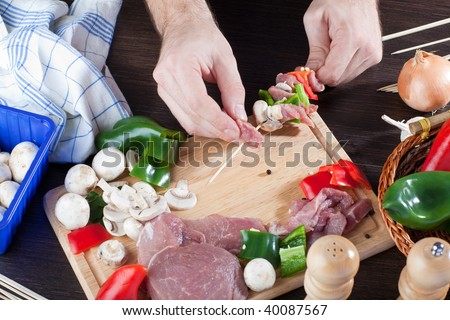 Person making meat sticks with veggies - stock photo
