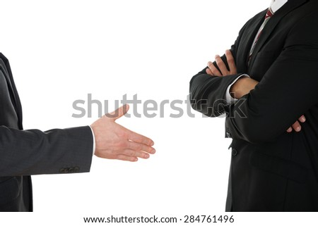 Person Offering Handshake To Businessman With Arm Crossed Over White Background - stock photo