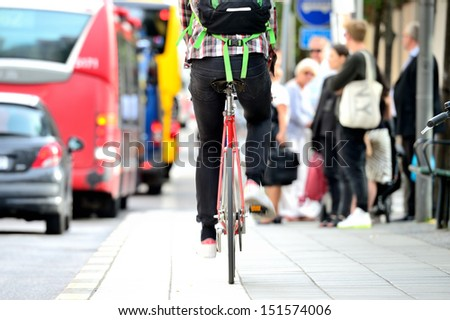 Person on bike in traffic - stock photo