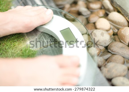 Person on scale with only feet to be seen on green lawn and wet pebble background. Person measures weight in spa setting. Health care and weight loss. Spa helps to be fit.