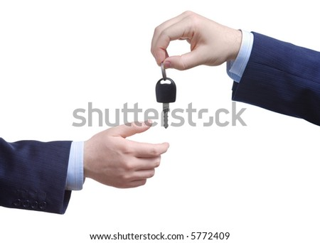 Person passing car key against white background - stock photo