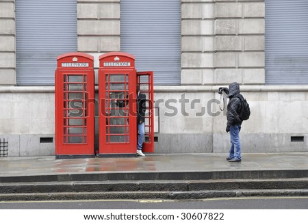 Person photographing a companion posing in a London phone booth - stock photo
