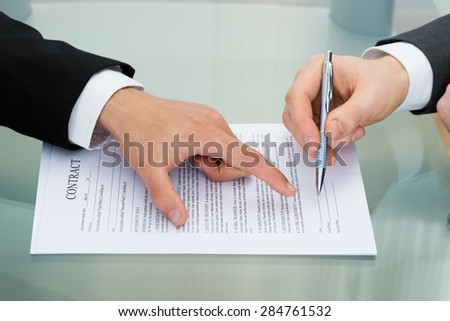 Person Pointing On Paper To Sign On Contract - stock photo