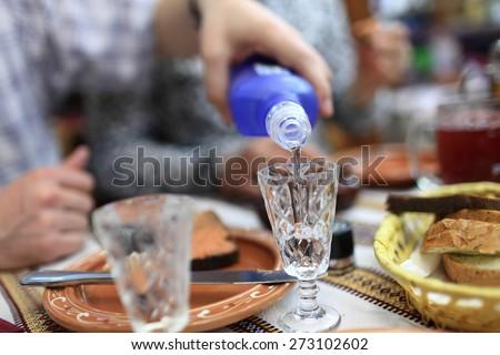 Person pouring vodka in the ukrainian restaurant - stock photo