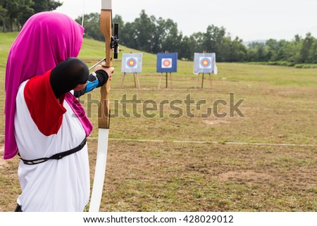Person practicing at outdoor archery target range, aiming at target board - stock photo