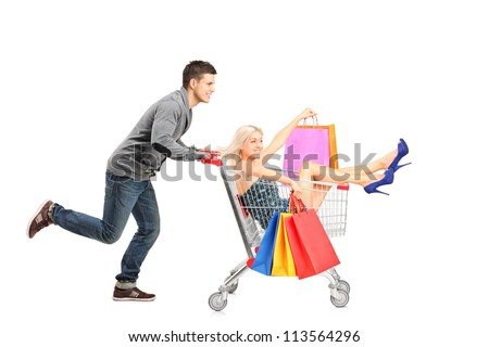 Person pushing a shopping cart, happy woman with bags in it, isolated on white background - stock photo