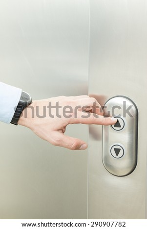 Person pushing up arrow elevator button. - stock photo