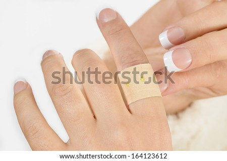 Person putting a plaster on finger isolated on white background - stock photo