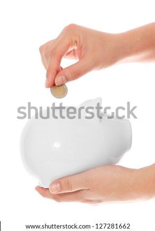 Person putting money into piggy bank. All on white background. - stock photo