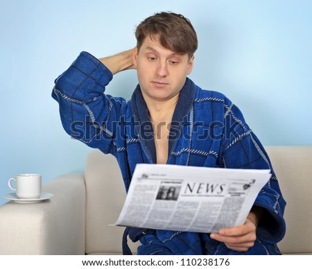Person reads a newspaper with pensiveness on blue background - stock photo