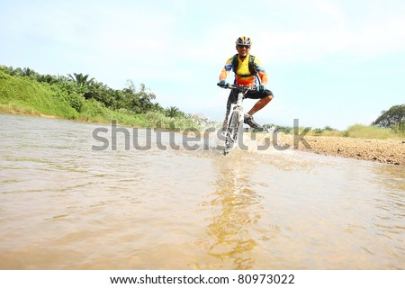Person riding a bike downhill  to the river - stock photo
