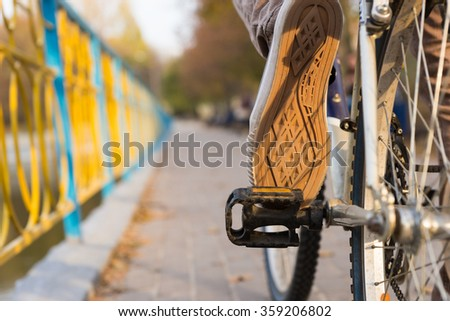 Person riding a bike outdoors on a walkway alongside a canal, close up view of the sole and underside of the shoe and the pedal - stock photo