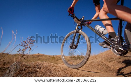 Person riding a mountain bike on a dirt track - stock photo
