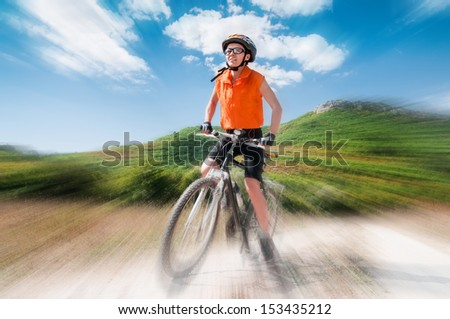 Person riding a mountiain bike on a slope with blur background - stock photo