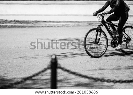 Person Riding Bicycle On An Urban Street In The City Of Washington D.C. On A Bright Sunny Day In Black & White Tone - stock photo