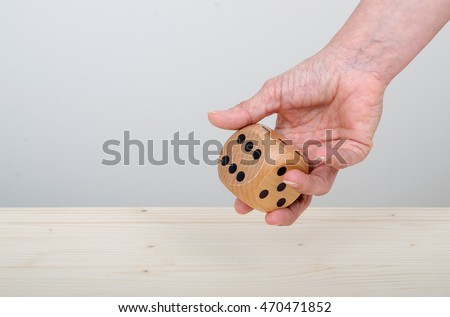 Person rolling a large Dice onto a wooden table. Landscape with copy space.