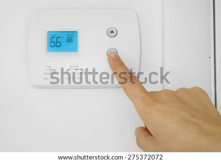Person's hand adjusting a wall mounted thermostat temperature                                - stock photo