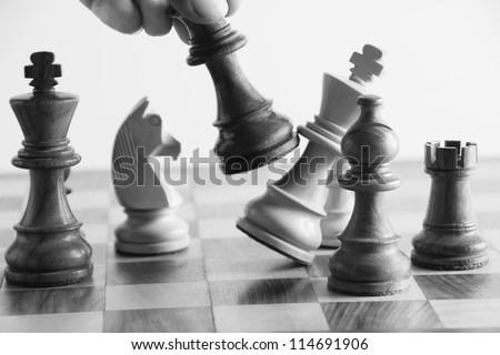 Person's hand defeating a king in the game of chess - stock photo