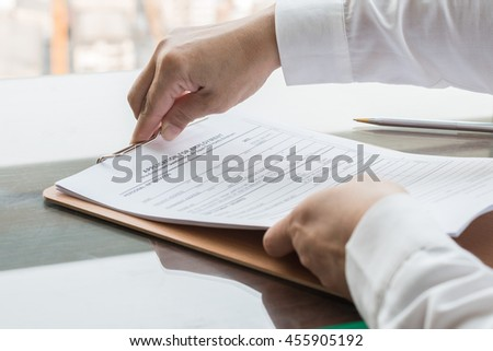 Person's hand filing blank application form paper w/ ballpoint pen on table: Fill in empty document template applying for job, finance, loan, mortgage or a claim for health, business insurance concept - stock photo
