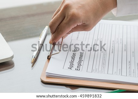 Person's hand filing blank application form paper w/ ballpoint pen on table: Fill in empty document template applying for job, finance, loan, mortgage or a claim for health, business insurance concept
