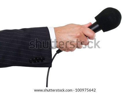 Person's hand holding a microphone - stock photo